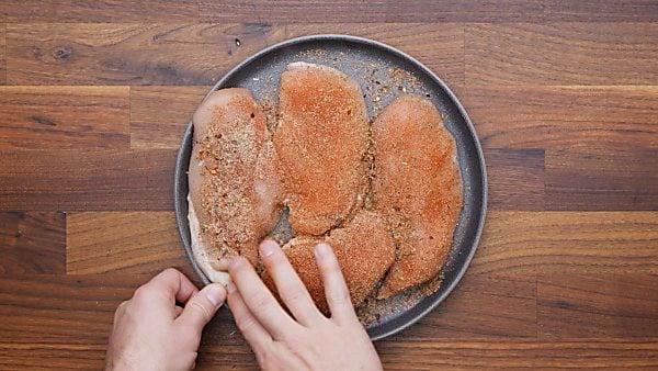 chicken breasts being seasoned on plate