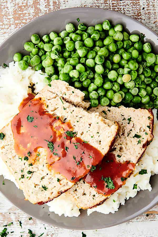 plate of chicken meatloaf on mashed potatoes with peas above