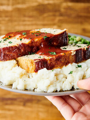 plate of chicken meatloaf on mashed potatoes held