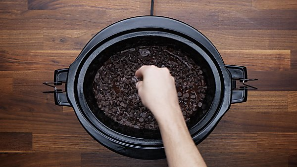 crockpot lava cake batter being topped with chocolate chips
