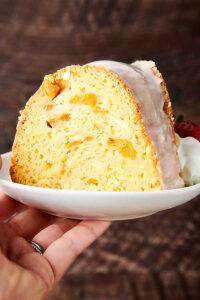 slice of peach pound cake on plate held