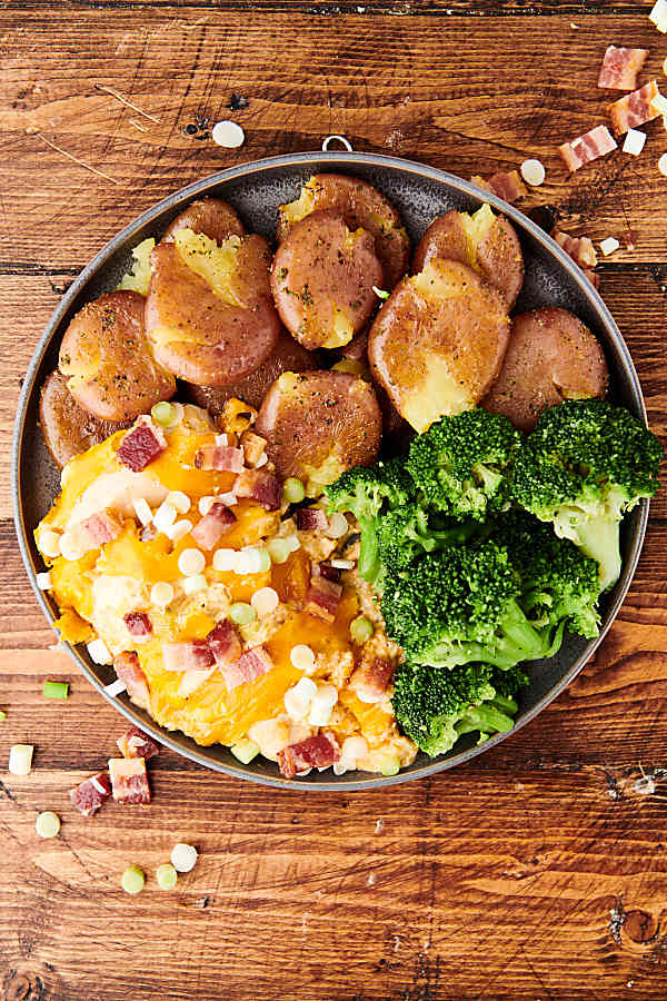 cream cheese chicken on a plate with potatoes and broccoli