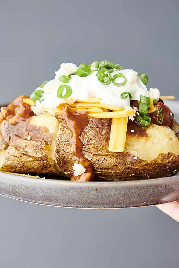 holding air fryer baked potato on a plate