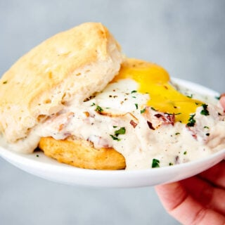 biscuit with bacon gravy on plate held